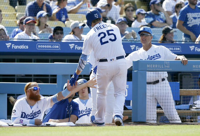 Los Angeles Dodgers' David Freese, center, is congratulated by Justin Turner, left, and coach Bob Geren, right, after scoring on a bases-loaded walk during the first inning of a baseball game against the Chicago Cubs in Los Angeles, Sunday, June 16, 2019. (AP Photo/Alex Gallardo)