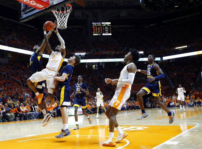 Tennessee guard Jordan Bone (0) goes to the basket as West Virginia forward Derek Culver (1) and guard Chase Harler (14) defend during the first half of an NCAA college basketball game Saturday, Jan. 26, 2019, in Knoxville, Tenn. (AP Photo/Wade Payne)