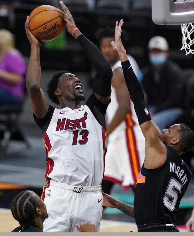 Miami Heat center Bam Adebayo (13) shoots over San Antonio Spurs guard Dejounte Murray (5) during the second half of an NBA basketball game in San Antonio, Wednesday, April 21, 2021. (AP Photo/Eric Gay)