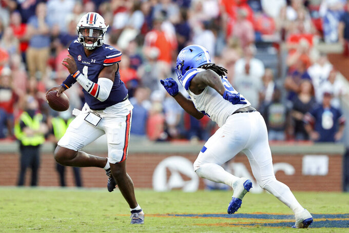 Auburn quarterback TJ Finley (1) scrambles away from Georgia State defensive end Tre Moore (54) during the second half of an NCAA football game Saturday, Sept. 25, 2021, in Auburn, Ala. (AP Photo/Butch Dill)