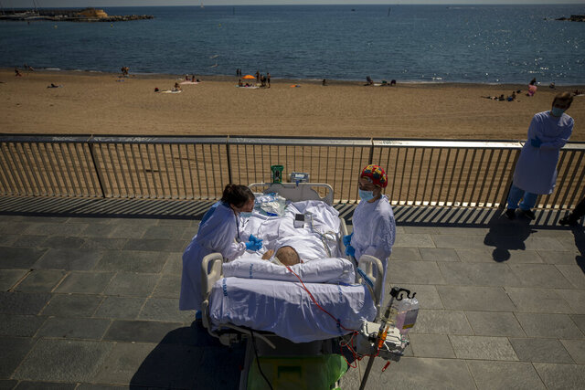 Francisco España, 60, is surrounded by members of his medical team as he looks at the Mediterranean sea from a promenade next to the