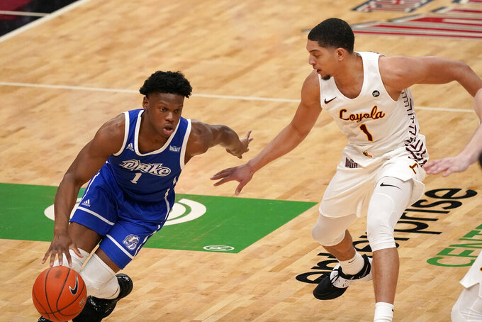 Drake's Joseph Yesufu heads to the basket past Loyola of Chicago's Lucas Williamson, right, during the first half of the championship game in the NCAA Missouri Valley Conference men's basketball tournament Sunday, March 7, 2021, in St. Louis. (AP Photo/Jeff Roberson)