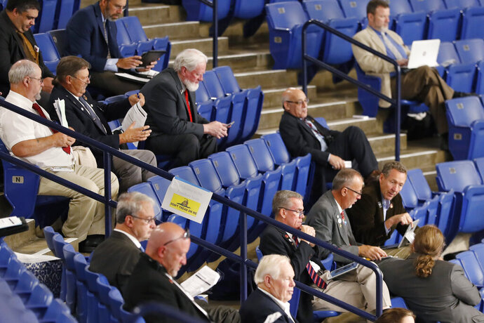 N.H. House of Representative members, who choose not wear a protective masks, sit in the