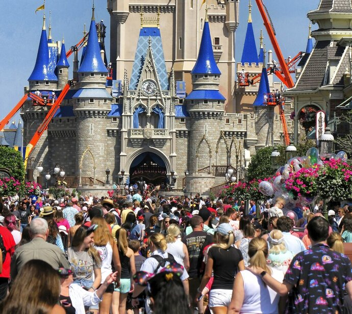 "FILE - In this March 12, 2020, file photo, a crowd is shown along Main Street USA in front of Cinderella Castle in the Magic Kingdom at Walt Disney World in Lake Buena Vista, Fla. As Walt Disney World prepares to allow some third-party shops and restaurants to open at its entertainment complex later this week, it's posting a warning. While enhanced safety measures are being taken at Disney Springs, ""an inherent risk of exposure to COVID-19 exists in any public place where people are present,"