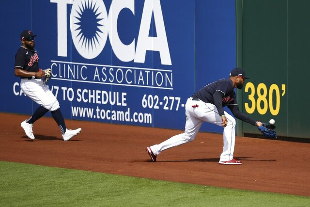 Cleveland Indians right fielder Domingo Santana, right, chases down a double hit by Los Angeles Dodgers' Tyler White as Indians center fielder Delino DeShields, left, watches during the fourth inning of a spring training baseball game Thursday, Feb. 27, 2020, in Goodyear, Ariz. (AP Photo/Ross D. Franklin)