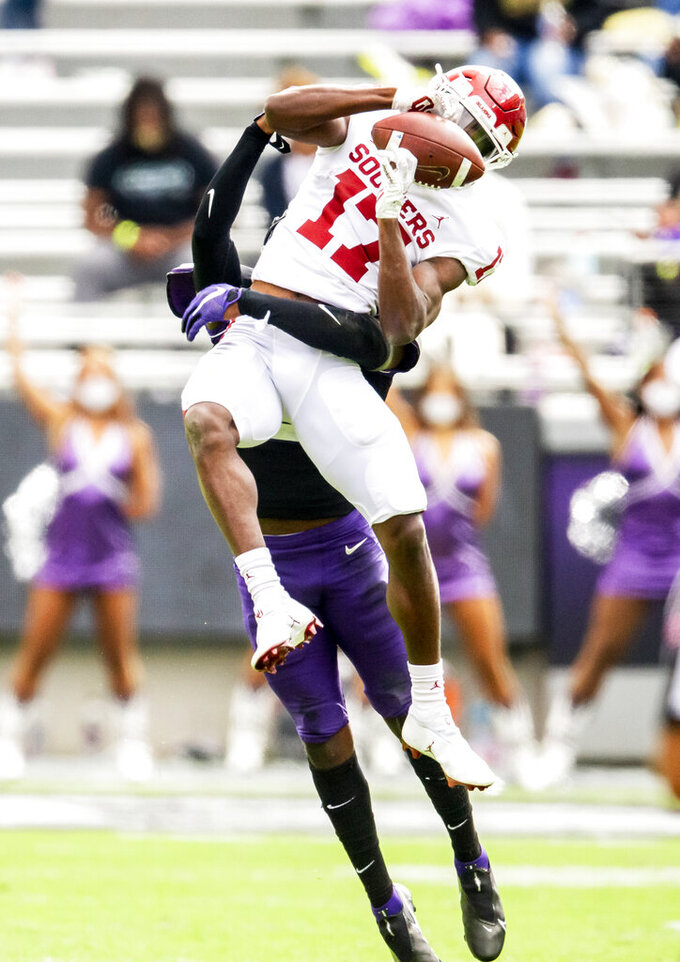 Oklahoma wide receiver Marvin Mims (17) catches a pass as TCU cornerback Kee'yon Stewart (2) defends during the first half of an NCAA College football game, Saturday, Oct. 24, 2020, in Fort Worth, Texas. (AP Photo/Brandon Wade)