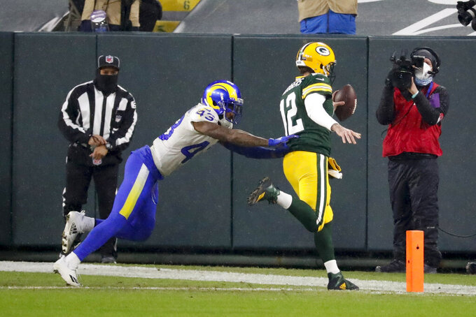 Green Bay Packers quarterback Aaron Rodgers (12) scores on a one-yard touchdown run past Los Angeles Rams' John Johnson during the first half of an NFL divisional playoff football game, Saturday, Jan. 16, 2021, in Green Bay, Wis. (AP Photo/Mike Roemer)