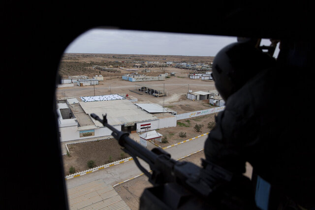 FILE - In this Dec. 29, 2019, file photo, an Iraqi soldier mans a machine gun onboard an army helicopter that is passing over the border town of al-Qaim during military operations of the Iraqi Army's Seventh Brigade, code named