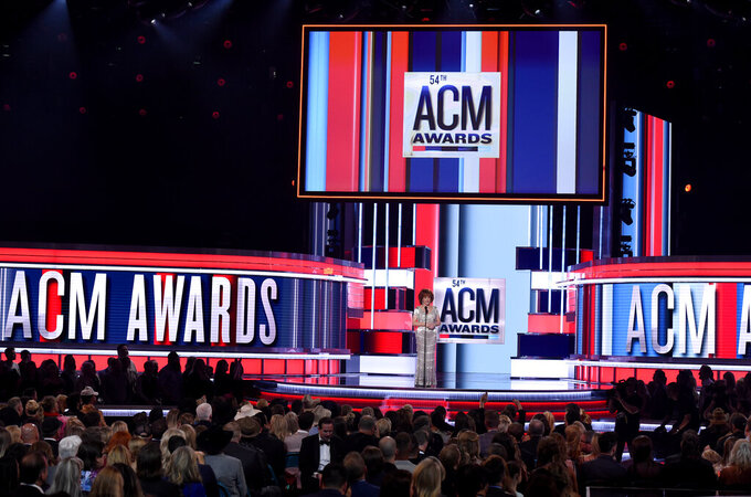 FILE - This April 7, 2019 file photo shows host Reba McEntire on stage at the 54th annual Academy of Country Music Awards in Las Vegas.  The Academy of Country Music Awards is coming back to Nashville in April for a second time to hold its awards show at three different venues. The show will air on April 18 on CBS from the Grand Ole Opry House, the Ryman Auditorium and the Bluebird Cafe. The show is normally held in Las Vegas every April, but moved to Music City last year when the coronavirus pandemic delayed their show to last September. (Photo by Chris Pizzello/Invision/AP, File)