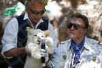 FILE - In this Thursday, July 17, 2014, file photo, Siegfried Fischbacher, left, holds up a white lion cub as Roy Horn holds up a microphone during an event to welcome three white lion cubs to Siegfried & Roy's Secret Garden and Dolphin Habitat, in Las Vegas. German news agency dpa is reporting that illusionist Siegfried Fischbacher, the surviving member of duo Siegfried & Roy has died in Las Vegas at age 81. The news agency said Thursday, Jan. 14, 2021 that Fischbacher's sister, a nun who lives in Munich, confirmed his death of cancer. (AP Photo/John Locher, File)