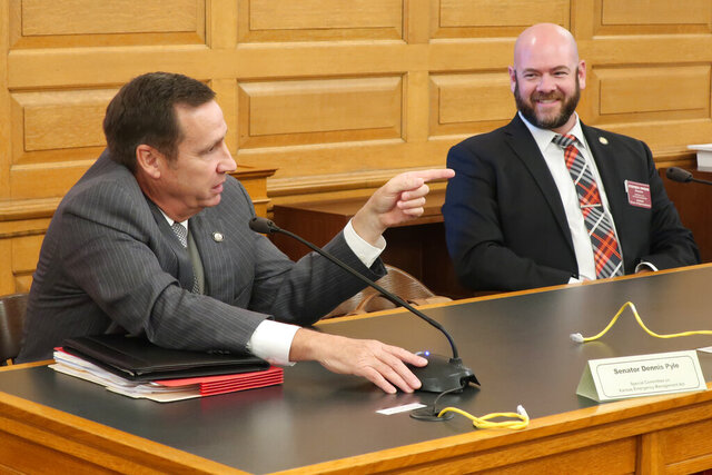 Kansas state Sen. Dennis Pyle, left, R-Hiawatha, left, makes a point at the end of a legislative committee meeting on the state's emergency management laws as Rep. Stephen Owens, R-Hesston, watches, Thursday, Sept. 24, 2020, at the Statehouse in Topeka, Kan. Both lawmakers favor broader legislative oversight of the governor's handling of long-term emergencies such as the coronavirus pandemic. (AP Photo/John Hanna)