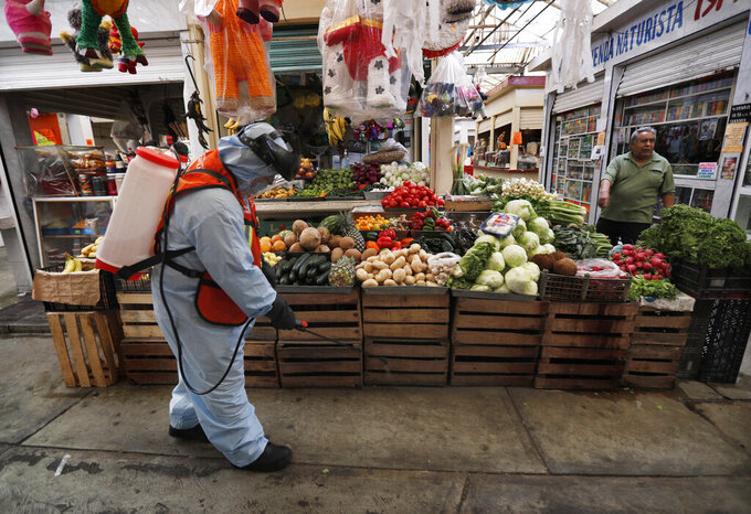 A member of a cleaning team wearing a protective mask and suit disinfects a showcase where fruit is sold, as a preventive measure against the spread of the new coronavirus, at the Iztapalapa market, in Mexico City, Thursday, April 2, 2020. Mexico has started taking tougher measures against the new coronavirus, but some experts warn the country is acting too late and testing too little to prevent the type of crisis unfolding across the border in the United States. (AP Photo/Marco Ugarte)