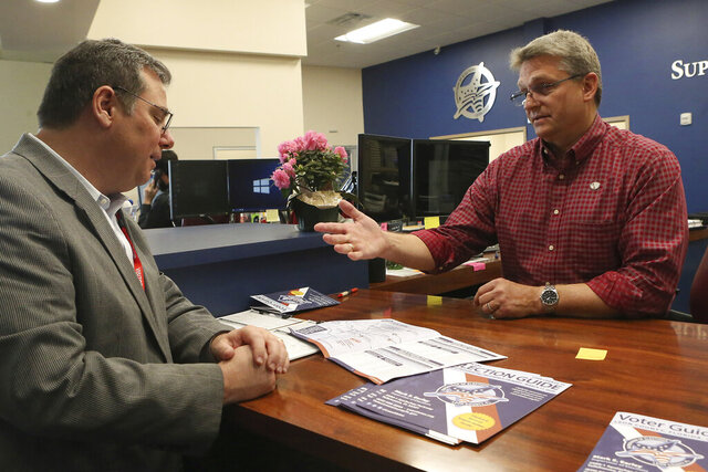 Leon County supervisor of elections Mark Earley, right, shows Don Palmer of the federal election assistance commission the sample ballot for the Tuesday primary on Thursday, March 12, 2020 in Tallahassee, Fla. (AP Photo/Steve Cannon)
