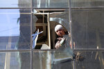 An Afghan worker removes the shuttered glasses of a shop near the site of Wednesday's attack in Kabul, Afghanistan, Thursday, May 9, 2019. Taliban fighters attacked the offices of a U.S.-based aid organization in the Afghan capital on Wednesday, setting off a huge explosion and battling security forces in an assault, the Interior Ministry said. (AP Photo/Rahmat Gul)