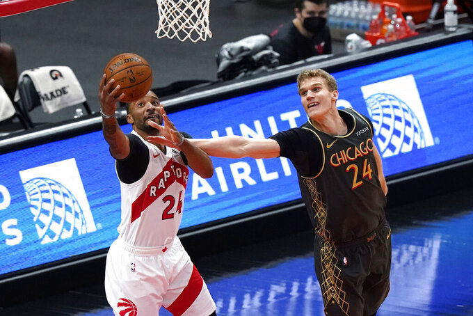 Toronto Raptors guard Norman Powell, left, drives to the basket against Chicago Bulls forward Lauri Markkanen during the first half of an NBA basketball game in Chicago, Sunday, March 14, 2021. (AP Photo/Nam Y. Huh)