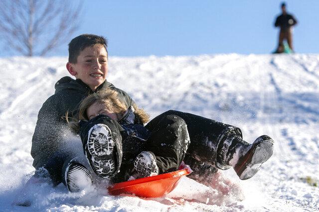 Luke Stanton, 12, and his sister, Hannah, 6, both of Lewiston, Idaho, sled hill at Sunset Park on Friday, Jan. 17, 2020, in Lewiston, Idaho. (Pete Caster/Lewiston Tribune via AP)