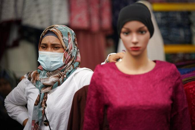 A Muslim vendor wearing protective mask waiting for customers at a Ramadan bazaar, amid the outbreak of the coronavirus disease (COVID-19) in Kuala Lumpur, Malaysia, Monday, April 19, 2021. (AP Photo/Vincent Thian)