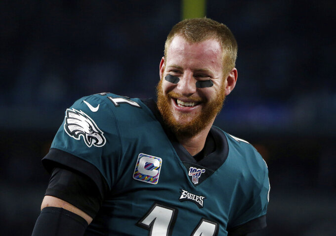 Philadelphia Eagles quarterback Carson Wentz (11) smiles as he talks with teammates during warmups before an NFL football game against the Dallas Cowboys in Arlington, Texas, Oct. 20, 2019. (AP Photo/Michael Ainsworth)