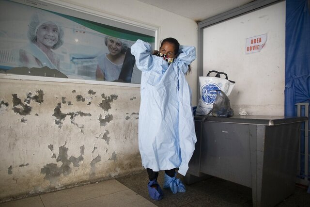 Elena Suazo, a kindergarten cafeteria worker, puts on the protective gear she brought from home, outside the entrance to the COVID-19 wing of José Gregorio Hernández Hospital which used to be the emergency room, as she prepares to enter and care for her 76-year-old hospitalized father, in the Catia neighborhood of Caracas, Venezuela, Thursday, Sept. 24, 2020. In this ruined country, the only way to ensure that he received the care he needed was to do it herself, regardless of the dangers to her own health. (AP Photo/Ariana Cubillos)