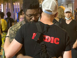 """A medic embraces activist D.J. Hooker after an SUV struck a parked car and tossed it into demonstrators during a protest in Minneapolis early Monday, June 14, 2021. A woman was killed and three others were injured. """"The car went through the air and it hit a young woman,"""" Hooker told Minnesota Public Radio. (Matt Sepic/Minnesota Public Radio via AP)"""