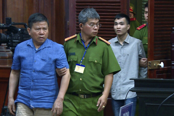 Australian man Chau Van Kham, left, is escorted into a court room in Ho Chi Minh city, Vietnam Monday, Nov. 11, 2019. Kham was sentenced to 12 years in jail for conducting activities of