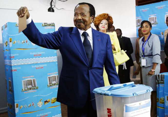 FILE - In this Sunday Oct. 7, 2018, file photo, Cameroon's incumbent President Paul Biya, of the Cameroon People's Democratic Movement party, casts his vote during the presidential elections in Yaounde, Cameroon. The United States says it's cutting military aid to Cameroon over human rights concerns after growing allegations of abuses by security forces. (AP Photo/Sunday Alamba, File)