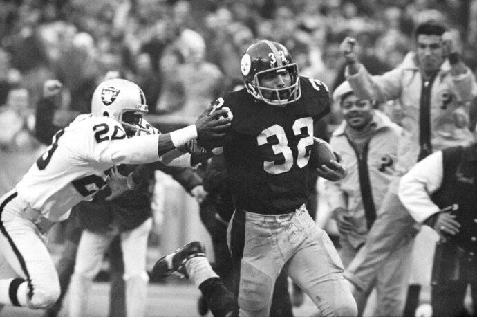 "FILE - In this Dec. 23, 1972, file photo, Pittsburgh Steelers' Franco Harris (32) eludes a tackle by Oakland Raiders' Jimmy Warren as he runs 42-yards for a touchdown after catching a deflected pass during an AFC Divisional NFL football playoff game in Pittsburgh. Harris' scoop of a deflected pass and subsequent run for the winning touchdown _ forever known as the ""Immaculate Reception"" _ has been voted the greatest play in NFL history. A nationwide panel of 68 media members chose the Immaculate Reception as the top play with 3,270 points and 39 first-place votes. (AP Photo/Harry Cabluck, File)"