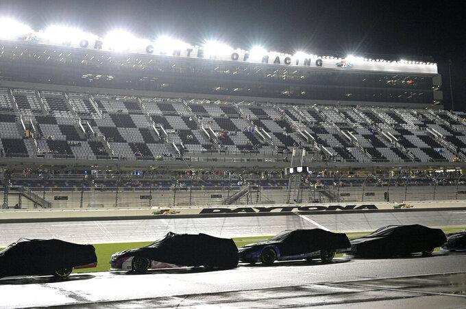 Cars sit covered on pit road after rain caused a postponement during a NASCAR Xfinity Series auto race at Daytona International Speedway, Friday, Aug. 27, 2021, in Daytona Beach, Fla. (AP Photo/Phelan M. Ebenhack)