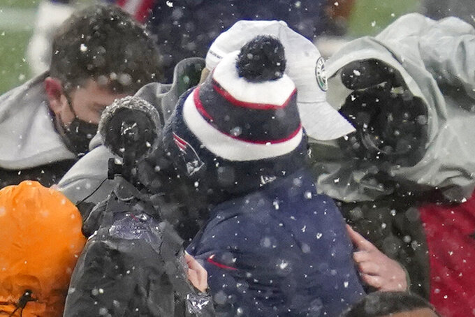 New York Jets head coach Adam Gase, rear wearing a white cap, and New England Patriots head coach Bill Belichick, front wearing a ski hat, embrace at midfield after an NFL football game, Sunday, Jan. 3, 2021, in Foxborough, Mass. (AP Photo/Charles Krupa)