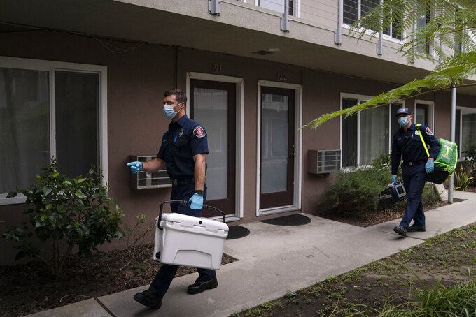 Torrance firefighter Trevor Borello, left, carries a cooler containing the Pfizer COVID-19 vaccine as he walks to an apartment to inoculate two sisters who have  muscular dystrophy, Wednesday, May 12, 2021, in Torrance, Calif. Teamed up with the Torrance Fire Department, Torrance Memorial Medical Center started inoculating people at home in March, identifying people through a city hotline, county health department, senior centers and doctor's offices, said Mei Tsai, the pharmacist who coordinates the program. (AP Photo/Jae C. Hong)