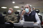 In this photo taken Monday, June 15, 2020, Turkish Defense Minister Hulusi Akar, right, and Chief of Staff Gen. Yasar Guler wearing face masks to protect against the coronavirus, monitor the operation at a military headquarters in Ankara, Turkey. Turkey said Wednesday it has airlifted troops for a cross-border ground operation against Kurdish militants in northern Iraq. The airborne offensive in Iraq's Haftanin region, some 15 kilometers (9 miles) from the border, was launched following