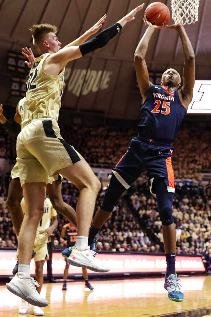Virginia guard Kody Stattmann (23) shoots next to Purdue center Matt Haarms (32) during the first half of an NCAA college basketball game in West Lafayette, Ind., Wednesday, Dec. 4, 2019. (AP Photo/Michael Conroy)