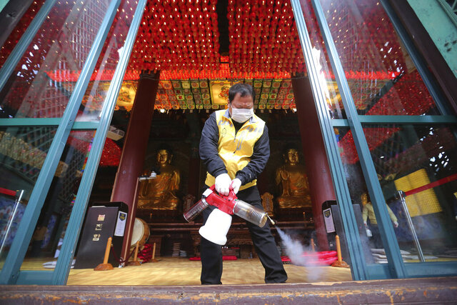 A resident of Jongno-Gu wearing a face mask sprays disinfectant as a precaution against the coronavirus at the Jogyesa Buddhist temple in Seoul, South Korea, Thursday, Feb.27, 2020. South Korea and China each reported Thursday the new illness persists in the worst-hit areas and spreads beyond borders. (AP Photo/Ahn Young-joon)