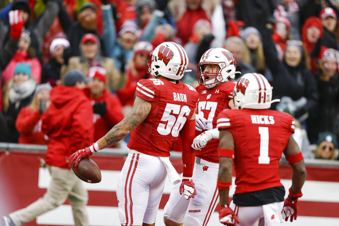 Wisconsin linebacker Zack Baun (56) celebrates an interception with teammates linebacker Jack Sanborn (57) and cornerback Faion Hicks (1) during the second half of an NCAA college football game against Michigan State Saturday, Oct. 12, 2019, in Madison, Wis. Baun scored a touchdown on the interception. Wisconsin won 38-0. (AP Photo/Andy Manis)