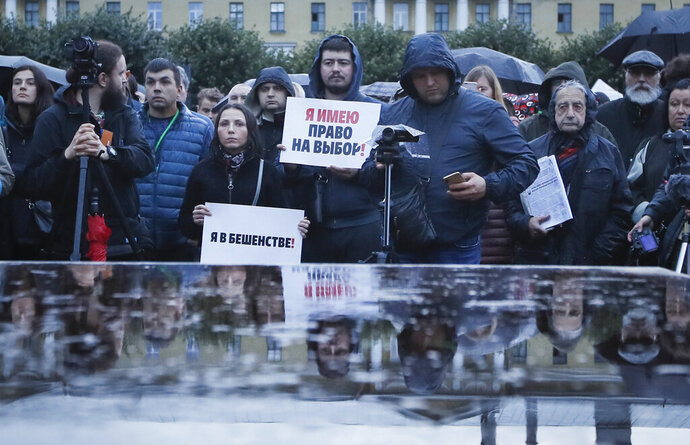 People gather for a meeting against the violations during governor and municipal elections in St.Petersburg, Russia, Tuesday, Sept. 17, 2019. The poster reads: 'I have the right to choose'. (AP Photo/Dmitri Lovetsky)