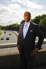 Tennessee State Rep. Harold Love, Jr. stands on an overpass over I-40, Monday, July, 19, 2021, near the site of his family's former home on the north side of Nashville, Tenn. Love Jr.'s father, a Nashville city councilman, was forced to sell his family home near this spot to make way for the highway, but put up a fight in the 1960s against the rerouting of Interstate 40 because he believed it would stifle and isolate Nashville's Black community. Love Jr. is now part of a group pushing to build a cap, across the highway behind. him, that creates a community space to help reunify the city. (AP Photo/John Amis)