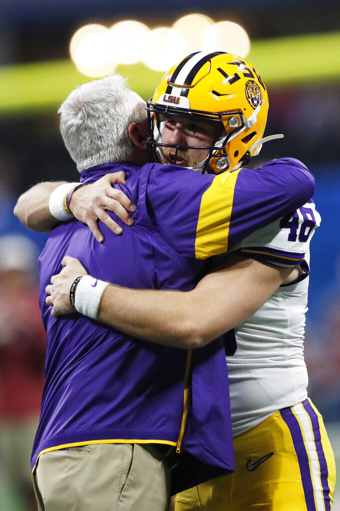 LSU Offensive Coordinator Steve Ensminger embracxes LSU long snapper Blake Ferguson (48) before the first half of the Peach Bowl NCAA semifinal college football playoff game between LSU and Oklahoma, Saturday, Dec. 28, 2019, in Atlanta. Ensminger's daughter-in-law, Carley McCord, died in a plane crash Saturday in Louisiana on the way to the game. (AP Photo/John Bazemore)