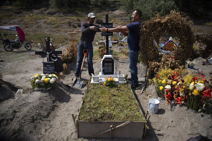 """Cemetery worker Jorge Arvizu, left, helps a family member place a plaque on the grave of Vicente Dominguez who died of complications related to the new coronavirus, at the municipal cemetery Valle de Chalco, on the outskirts of Mexico City, Tuesday, Oct. 20, 2020. Mexican families traditionally flock to local cemeteries tohonor their dead relatives as part of the """"Dia de los Muertos,"""" or Day of the Dead celebrations, but according to authorities the cemeteries will be closed this year to help curb the spread of COVID-19. (AP Photo/Marco Ugarte)"""