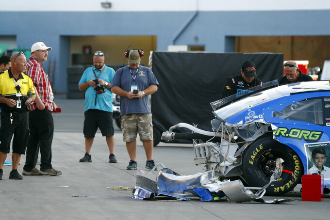 Fans take photos of Joey Gase's damaged car in the garage area during a NASCAR Cup Series auto race at the Las Vegas Motor Speedway Sunday, Sept. 26, 2021, in Las Vegas. Gase crashed during the race and was taken to a local hospital. (AP Photo/Steve Marcus)