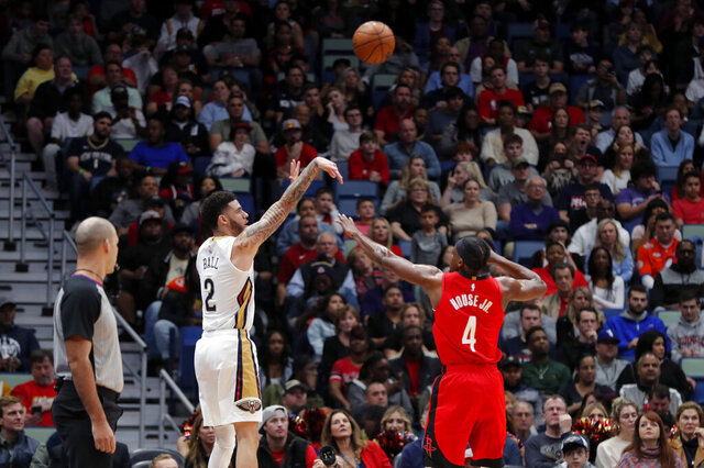 New Orleans Pelicans guard Lonzo Ball (2) shoots a three-point basket against Houston Rockets forward Danuel House Jr. (4) in the first half of an NBA basketball game in New Orleans, Sunday, Dec. 29, 2019. (AP Photo/Gerald Herbert)