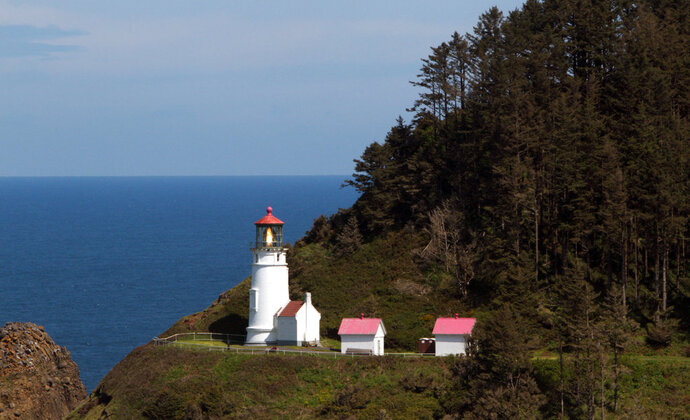 FILE - This May 13, 2011 file photo shows the Heceta Head Lighthouse on the Oregon coast near Yachats, Ore. The lighthouse will shut down for July, 2018, for repair work. The Oregon Parks and Recreation Department says repairs will address several cracked interior metal columns on the facility's upper floor and will cost about $135,000. (AP Photo/The Oregonian, Randy L. Rasmussen, file)