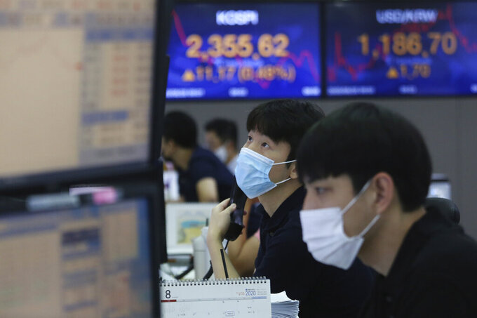 A currency trader watches monitors at the foreign exchange dealing room of the KEB Hana Bank headquarters in Seoul, South Korea, Friday, Aug. 28, 2020. Asian markets were mostly higher Friday after the Federal Reserve said it might keep interest rates low even if inflation rises, in a major overhaul to its strategy. (AP Photo/Ahn Young-joon)