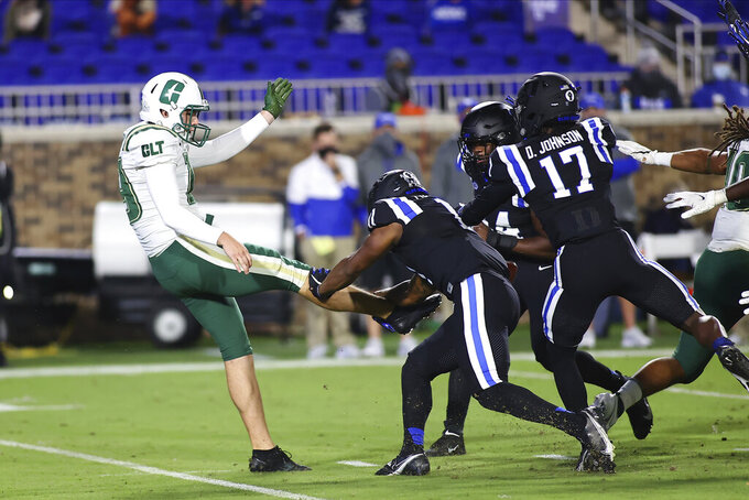 Charlotte's Connor Bowler (19) has his punt blocked blocked by Duke's Isaiah Fisher-Smith (11) during the first quarter of an NCAA college football game Saturday, Oct. 31, 2020, in Durham, N.C. (Jaylynn Nash/Pool Photo via AP)