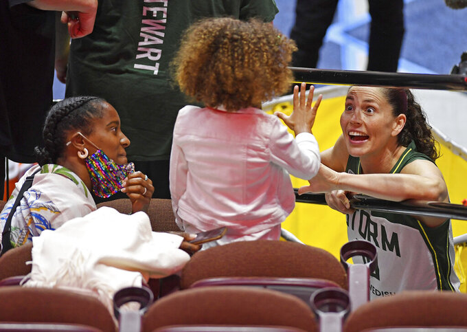 Connecticut women's basketball alumna and Seattle Storm star Sue Bird, right, talks to Ruby Randle, 5, and her mother Jaime, left, following a Storm win over the Connecticut Sun in a WNBA basketball game Sunday, June 13, 2021, at Mohegan Sun Arena in Uncasville, Conn. Jaime, also a Connecticut alumna and friend of former UConn player Tina Charles, met Bird through Charles and this was Ruby's first chance to meet Bird. (Sean D. Elliot/The Day via AP)