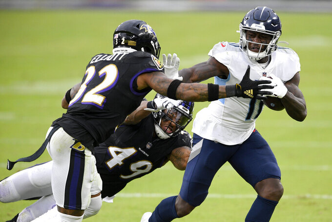 Tennessee Titans wide receiver A.J. Brown (11) runs with the ball as Baltimore Ravens linebacker Chris Board (49) and free safety DeShon Elliott (32) try to stop him during the second half of an NFL football game, Sunday, Nov. 22, 2020, in Baltimore. (AP Photo/Nick Wass)