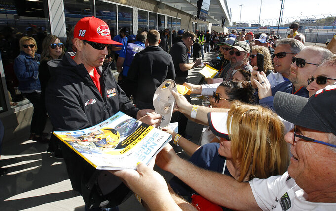 Kyle Busch (18) signs autographs for fans outside the drivers meeting room prior to the start of the NASCAR Cup Series auto race at ISM Raceway, Sunday, March 10, 2019, in Avondale, Ariz. (AP Photo/Ralph Freso)