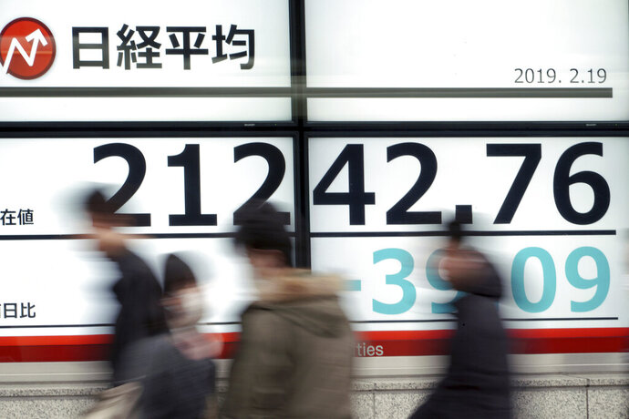 People walk past an electronic stock board showing Japan's Nikkei 225 index at a securities firm in Tokyo Tuesday, Feb. 19, 2019. Asian shares are mostly higher as Chinese and U.S. officials prepare for trade talks in Washington this week. (AP Photo/Eugene Hoshiko)