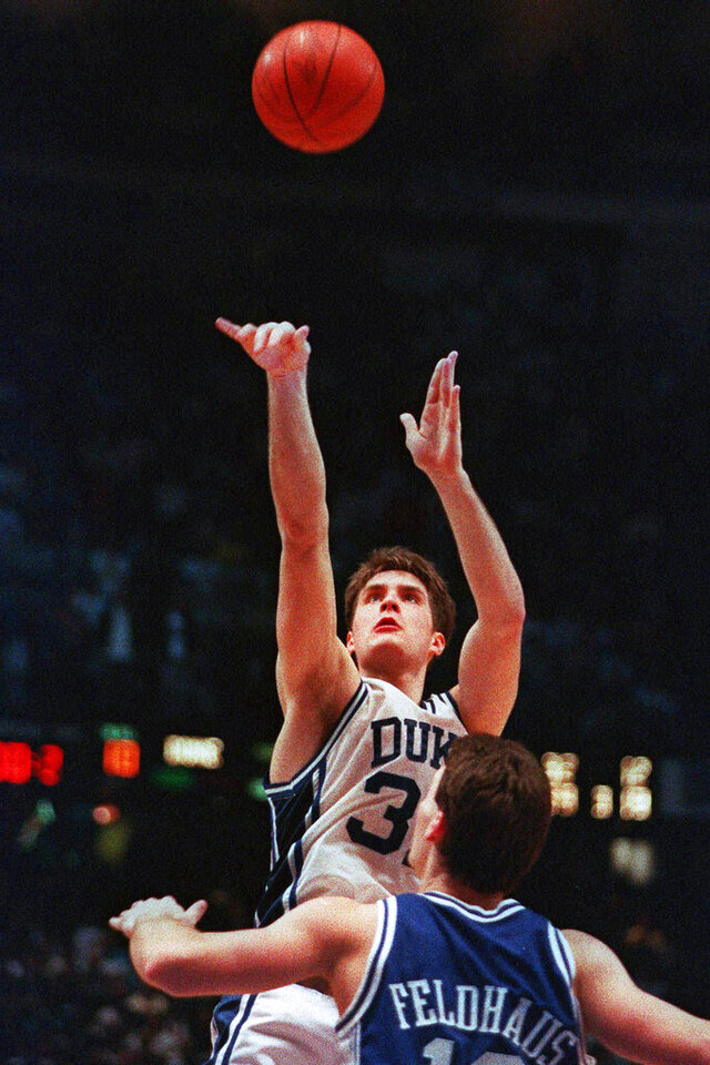 FILE - In this March 28, 1992, file photo, Duke's Christian Laettner takes the winning shot in overtime over Kentucky's Deron Feldhaus for a 104-103 victory in the East Regional final NCAA college basketball game in Philadelphia. A panel of Associated Press sports writers voted in March 2020 on the top 10 men's basketball games in the history of the NCAA Tournament. They are being republished because the sport has been shut down because of the coronavirus pandemic. The Duke vs Kentucky game on March 28, 1992, was voted No. 2. (AP Photo/Charles Arbogast, File)
