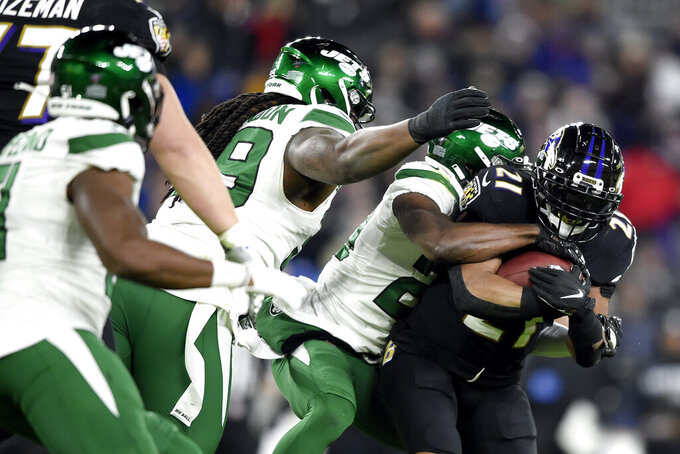 Baltimore Ravens running back Mark Ingram, right, is wrapped up by New York Jets free safety Marcus Maye, second from right, during the first half of an NFL football game, Thursday, Dec. 12, 2019, in Baltimore. (AP Photo/Gail Burton)