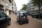 A man drives his small cart into a garage in Knokke, Belgium, Tuesday, Aug. 11, 2020. At the seaside resort of Knokke-Heist, where golf carts with license plates ply well-kept streets, there was ample room to stretch out on the local beach this week. Local authorities have banished day trippers from Belgian cities or France from its 15-kilometer (10-mile) stretch of sands until the heat wave is over. (AP Photo/Virginia Mayo)